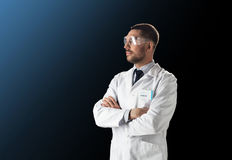 Scientist in lab coat and safety glasses. Science, technology and people concept - male doctor or scientist in white lab coat and safety glasses over black Royalty Free Stock Photography