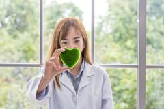 Science whit green spirit mind. Green heart in her hand on lab a background. Beautiful smiling female doctor or Scientist holding royalty free stock photo