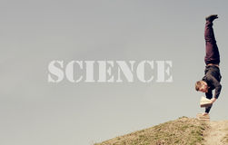 SCIENCE word - Guy standing on his head and reading Stock Image