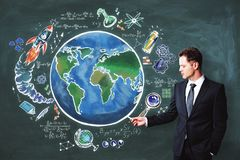 Science and world backdrop. Handsome european businessman drawing creative globe sketch on chalkboard backdrop. Science and world concept royalty free stock images