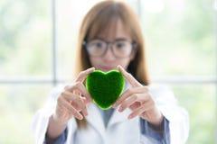 Sciene-Whitgrün-Geistverstand Grünes Herz in ihrer Hand auf Labor ein Hintergrund Schöne lächelnde Ärztin oder Wissenschaftler, d stockbilder