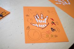 scientific activity for children, drawing and collage of the bones of the hand. On a decorated orange sheet a hand was drawn and stock image