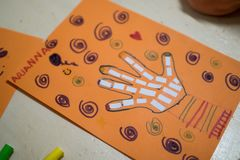 scientific activity for children, drawing and collage of the bones of the hand. On a decorated orange sheet a hand was drawn and stock images