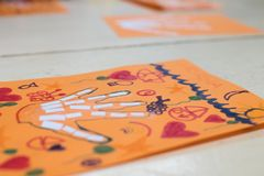 scientific activity for children, drawing and collage of the bones of the hand. On a decorated orange sheet a hand was drawn and royalty free stock photography