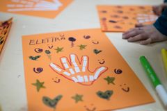 scientific activity for children, drawing and collage of the bones of the hand. On a decorated orange sheet a hand was drawn and royalty free stock photo