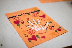 scientific activity for children, drawing and collage of the bones of the hand. On a decorated orange sheet a hand was drawn and stock photography