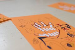 scientific activity for children, drawing and collage of the bones of the hand. On a decorated orange sheet a hand was drawn and royalty free stock images