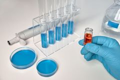 Scientific background in blue, white and orange. Liquid sample in female hand, blue liquid samples in glass tubes and dishes Stock Photography