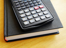 Scientific calculator on book Stock Photo