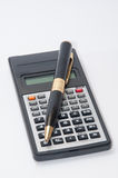 Scientific calculator and golden pen Royalty Free Stock Photos