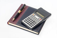 Scientific calculator and golden pen on business notebook Stock Photo
