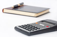 Scientific calculator and golden pen on business notebook Royalty Free Stock Photography