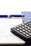 Scientific calculator on the maths workbook with blue pen Stock Photo