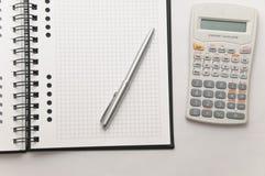 Scientific calculator next to elegant silver pen Stock Photos