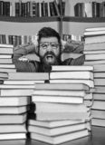 Scientific discovery concept. Teacher or student with beard wears eyeglasses, sits at table with books, defocused. Man. On shocked face between piles of books royalty free stock photo