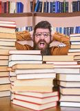 Scientific discovery concept. Teacher or student with beard wears eyeglasses, sits at table with books, defocused. Man. On shocked face between piles of books stock photos