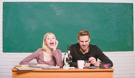 Scientific experiment. Guy and girl at desk with microscope. Studying in college or university. Biology lesson. Students royalty free stock images