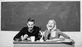 Scientific experiment. Guy and girl at desk with microscope. Studying in college or university. Biology lesson. Students. Studying university. Genetics and stock image
