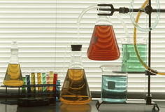 Scientific glassware with colored liquids. Scientific glassware and tubes filled with colored liquids against window blinds Royalty Free Stock Photos