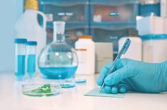 Scientific or medical background with gloved hand holdong micros Stock Image
