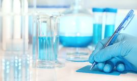 Scientific or medical background with gloved hand holdong micros Royalty Free Stock Photography