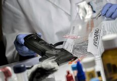 Scientific police officer examining traces of a gun in ballistic laboratory stock image