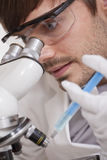 Scientific Research. Man looking in microscope with syringe in his hand Stock Photography