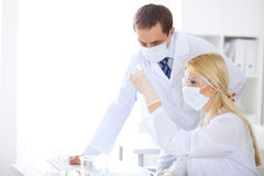 Scientific research team with clear solution in laboratory Stock Photo