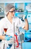 Scientific researcher in a lab. Scientific researcher holding at a liquid solution in a lab Stock Photo