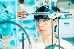 Scientific researcher in a lab. Scientific researcher holding at a liquid solution in a lab Royalty Free Stock Photo