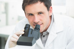 Scientific researcher using microscope in the laboratory. Close up portrait of a male scientific researcher using microscope in the laboratory Stock Photo