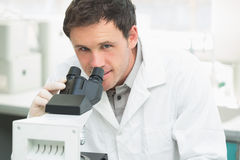 Scientific researcher using microscope in the laboratory. Close up portrait of a male scientific researcher using microscope in the laboratory Stock Photos