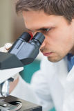 Scientific researcher using microscope in the laboratory. Extreme Close up of a male scientific researcher using microscope in the laboratory Stock Photo