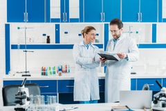 Scientific researchers in white coats and eyeglasses with notepad. In laboratory royalty free stock photography