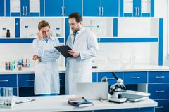 Scientific researchers in white coats and eyeglasses with notepad. In laboratory stock photo