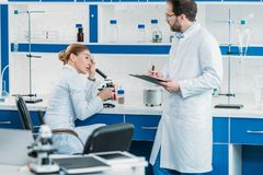 Scientific researchers in white coats and eyeglasses working together. In laboratory stock images