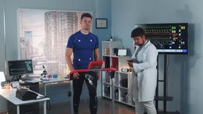 Cargiologist coming to monitor athlete`s stress testing on treadmill. Scientific Sports Laboratory: Cargiologist coming to monitor athlete`s stress testing on stock video