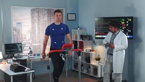 Scientific sports laboratory: doctor coming to monitor athlete`s stress testing. The displays in lab showing EKG data stock footage