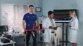 Two mixed race doctors discussing EKG data of athlete doing treadmill test in sports lab. Scientific Sports Laboratory: Two mixed race doctors discussing EKG stock footage