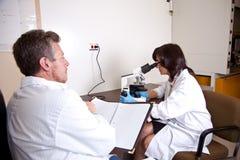 Scientific team performs research. Scientisfic team performs research with microscope Stock Photography