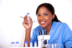 Scientific woman looking at you holding test tube. Scientific woman looking at you holding a test tube in blue uniform Stock Photos