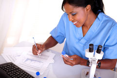 Scientific woman working with test tube and notes Stock Image