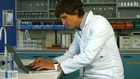 Scientifique à l'aide de l'ordinateur portable tout en écrivant sur le papier clips vidéos