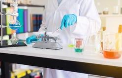 Scientifique à l'aide des pinces pesant la médecine ou l'échantillon médical de produits chimiques dans le tube à essai au labora photos libres de droits