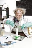 Scientifique aîné stupéfait avec le becher de émulsion Photographie stock libre de droits