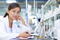 Scientifique asiatique de laboratoire travaillant au laboratoire avec des tubes à essai Images stock
