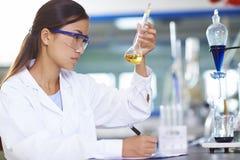 Scientifique asiatique de laboratoire travaillant au laboratoire avec des tubes à essai Image stock
