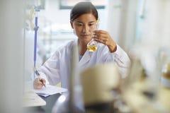Scientifique asiatique de laboratoire travaillant au laboratoire avec des tubes à essai Photographie stock libre de droits