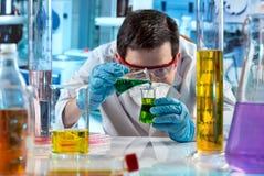 Scientifique avec des tubes à essai mélangeant des fluides dans le laboratoire image libre de droits