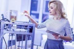 Scientifique blond heureux examinant la technologie moderne dans le bureau images stock